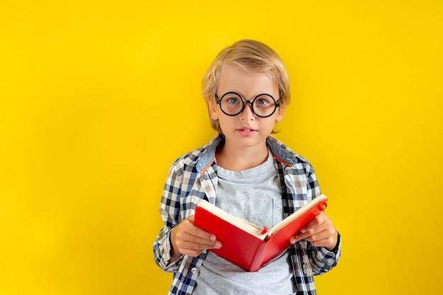 Porträt des niedlichen und klugen blonden kaukasischen jungen in einem karierten hemd auf gelbem hintergrund. 1. september tag. bildung und schulanfangskonzept. kinderschüler bereit zu lernen und zu lernen.