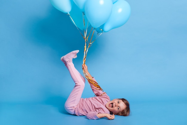 Porträt des niedlichen vorschulkindes, das gegen blaue wand mit luftballons aufwirft