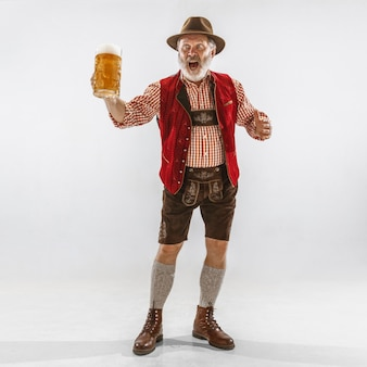Porträt des oktoberfest-älteren mannes im hut, der die traditionelle bayerische kleidung trägt. männlicher schuss in voller länge im studio auf weißem hintergrund. die feier, feiertage, festivalkonzept. bier trinken.