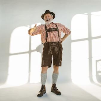 Porträt des oktoberfest-älteren mannes im hut, der die traditionelle bayerische kleidung trägt. männlicher schuss in voller länge im studio auf weißem hintergrund. die feier, feiertage, festivalkonzept. viel spaß beim anrufen.