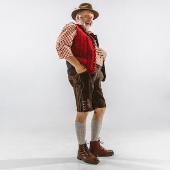 Porträt des oktoberfest-älteren mannes im hut, der die traditionelle bayerische kleidung trägt