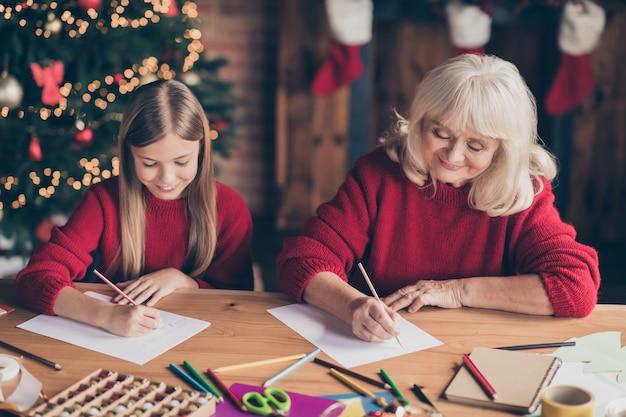Porträt des oma-enkelkindes, das wunschliste auf tisch am dekorierten haus schreibt
