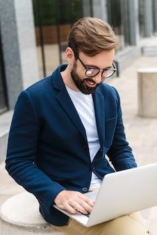 Porträt des optimistischen geschäftsmannes, der brillen trägt und laptop beim sitzen im freien nahe gebäude trägt