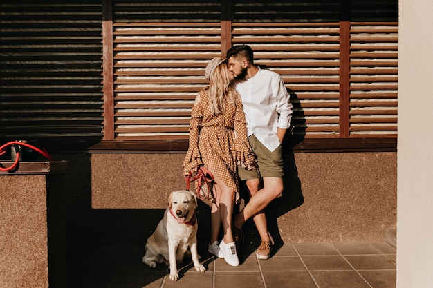 Porträt des paares, das auf hölzernem hintergrund küsst. mädchen im gepunkteten kleid und ihr modischer bärtiger kerl, der mit hund aufwirft.