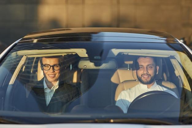Porträt des paares, das in die kamera lächelt, während es im auto sitzt und fährt
