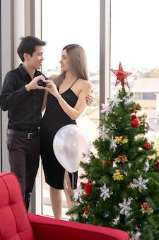 Porträt des paares, das neujahrs- und weihnachtsfestfeiertag im wohnzimmer der großen modernen wohnung feiert