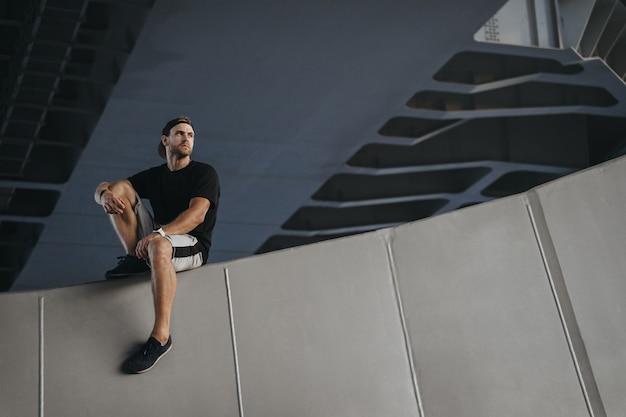 Porträt des parkour-athleten, der am rand der wand nach hartem freerunning sitzt