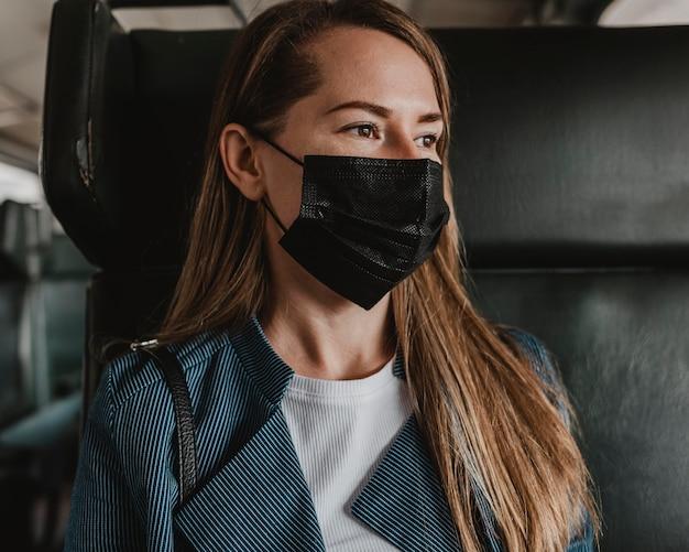Porträt des passagiers im zug, der medizinische maske trägt
