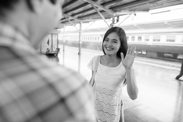 Porträt des persischen touristenmannes und der jungen schönen asiatischen touristenfrau zusammen am bahnhof in schwarzweiss