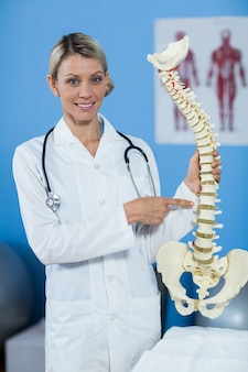Porträt des physiotherapeuten, der wirbelsäulenmodell hält