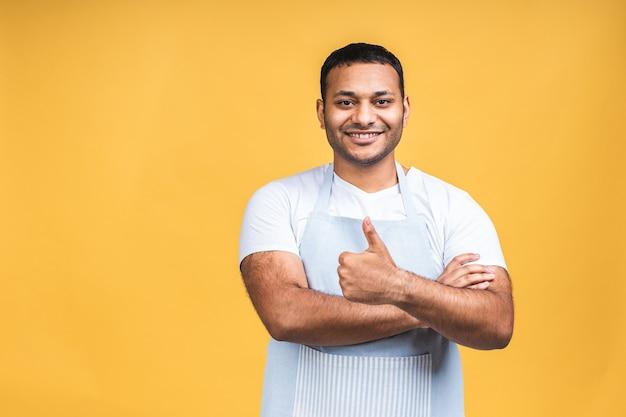Porträt des positiven attraktiven afroamerikanischen schwarzen indischen kochmannes in der schürze, die kamera lokalisiert über gelbem hintergrund betrachtet. daumen hoch.