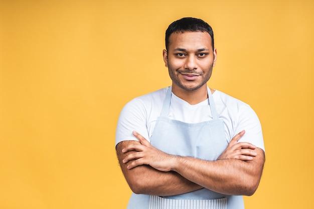 Porträt des positiven attraktiven afroamerikanischen schwarzen indischen kochmannes in der schürze, die kamera lokalisiert über gelbem hintergrund betrachtet.