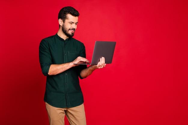 Porträt des positiven fröhlichen arbeiters, der copyspace unter verwendung seines laptops hat, der jobwerkstatt mit kollegen hat, tragen lässige art braune hosenhose