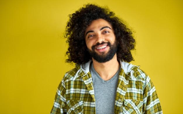 Porträt des positiven fröhlichen lockigen arabischen mannes im lässigen hemd lachend