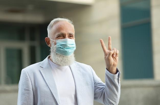 Porträt des positiven gutaussehenden älteren geschäftsmannes mit der medizinischen maske, die freundlich lächelt und hand winkt