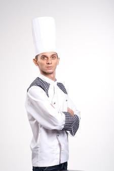 Porträt des positiven gutaussehenden kochkochs in der baskenmütze und im weißen outfit lokalisiert auf weißem hintergrund.