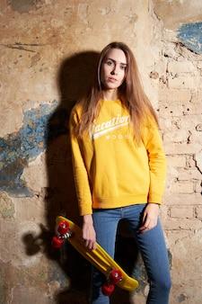 Porträt des positiven jungen attraktiven mädchens, das die gelbe bluse und blue jeans halten gelbes skateboard trägt.