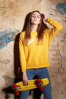 Porträt des positiven jungen attraktiven mädchens, das gelbe bluse und blaue jeans hält, die gelbes skateboard halten.