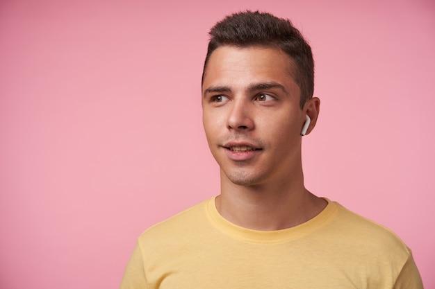 Porträt des positiven jungen gutaussehenden kurzhaarigen brünetten mannes mit ohrhörer, der wunderbar beiseite schaut, während er über rosa hintergrund mit händen unten steht