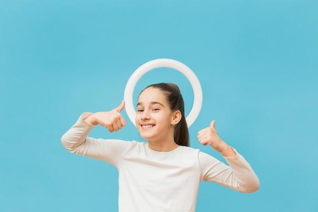 Porträt des positiven jungen mädchens, das daumen hoch zeigt