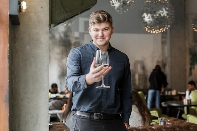 Porträt des positiven jungen mannes, der ein glas wein hält