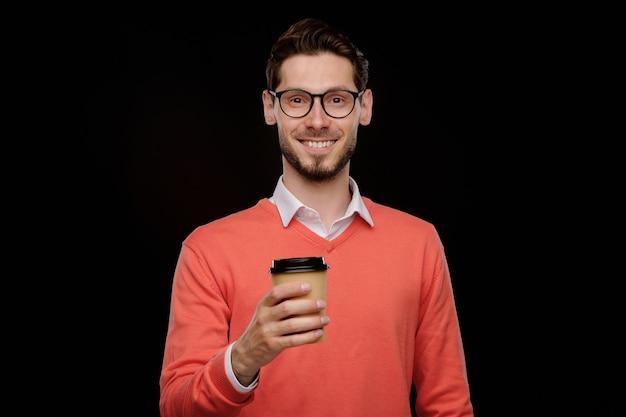 Porträt des positiven jungen mannes im orangefarbenen pullover, der kaffee trinkt, um gegen schwarzen hintergrund zu gehen