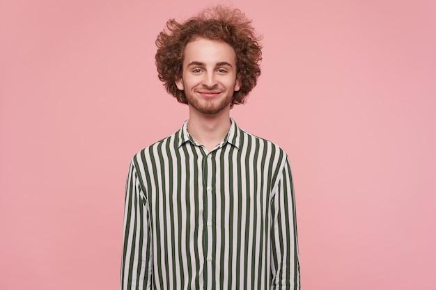 Porträt des positiven jungen niedlichen lockigen rothaarigen kerls mit dem angenehmen lächeln, das gestreiftes hemd trägt, während er über rosa wand steht und seine hände entlang körper hält