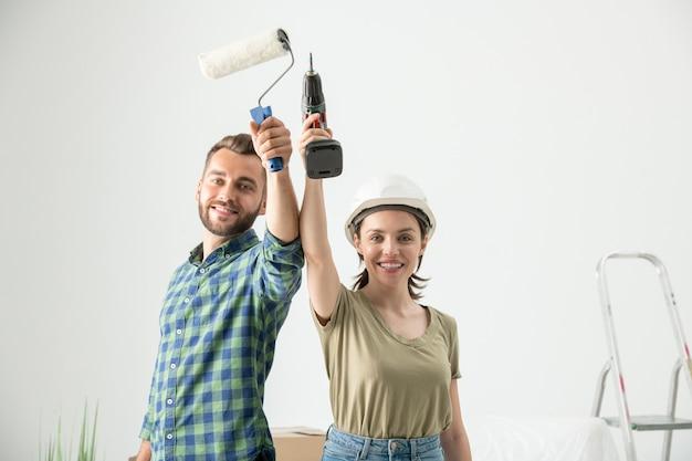 Porträt des positiven jungen paares, das umbauwerkzeuge aufhebt, während zur reparatur in der neuen wohnung bereit ist