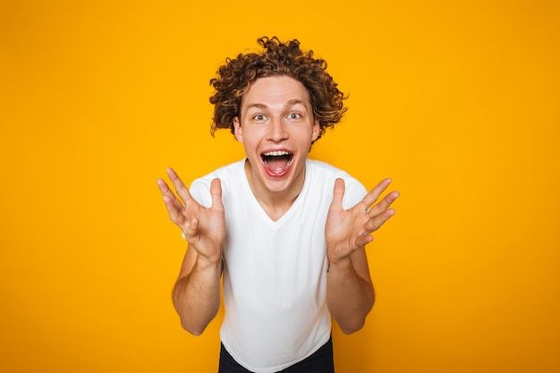 Porträt des positiven kerls mit dem gelockten braunen haar, das mit erhobenen händen zum gesicht schreit