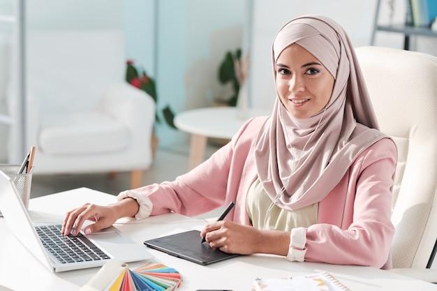Porträt des positiven kreativen jungen muslimischen webdesigners im hijab unter verwendung des laptops und des zeichenblocks im büro