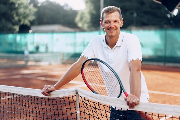 Porträt des positiven männlichen tennisspielers mit schläger, der am sandplatz steht