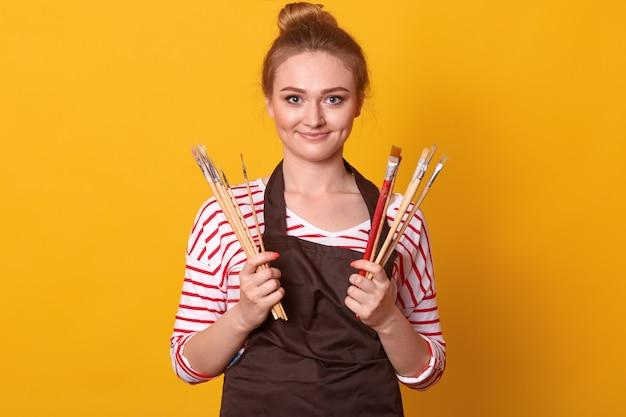 Porträt des positiven magnetischen jungen malers, der über gelb im studio aufwirft und pinselbündel in beiden händen hält