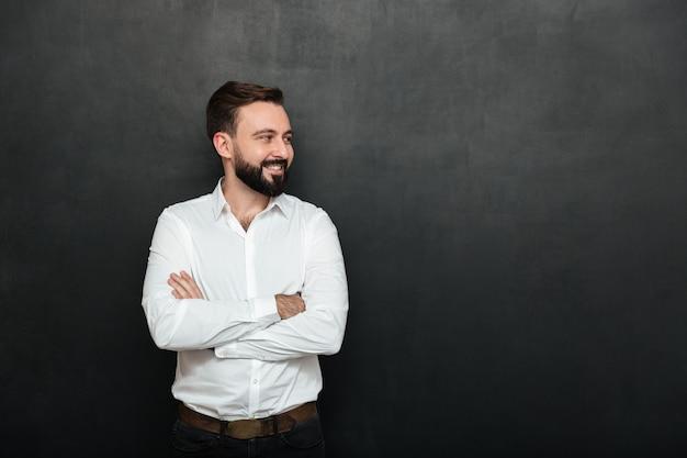 Porträt des positiven mannes im weißen hemd, das mit den armen gefaltet steht und weg über dunkelgrauem kopienraum schaut