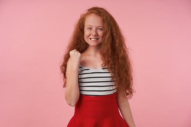 Porträt des positiven rothaarigen weiblichen teenagers mit dem langen lockigen haar, das hand in ja-geste anhebt, freudig zur kamera schauend und ihre weißen zähne zeigend, lokalisiert über rosa hintergrund