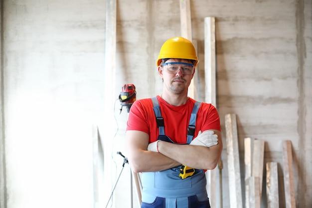 Porträt des professionellen arbeiters, der mit verschränkten armen in der schutzuniform und im gelben helm aufwirft. qualifizierter vorarbeiter beim bau eines neuen projekts. baustelle und renovierungskonzept