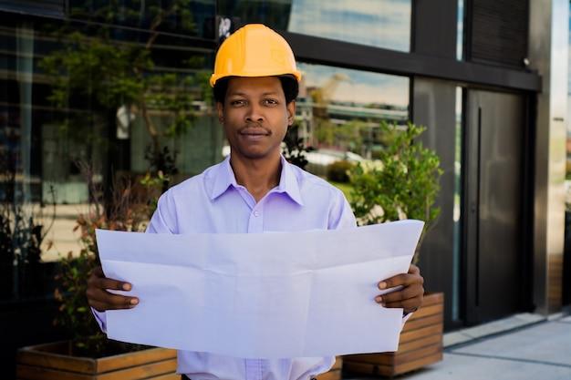 Porträt des professionellen architekten im helm, der blaupausen außerhalb des modernen gebäudes betrachtet. ingenieur- und architektenkonzept.
