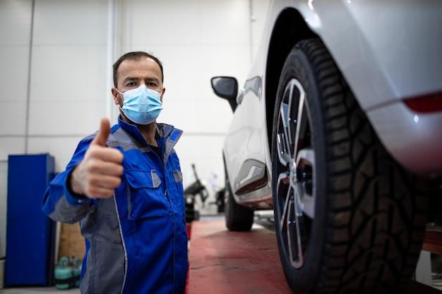 Porträt des professionellen automechanikers, der gesichtsmaske wegen des coronavirus trägt, der in der fahrzeugwerkstatt durch ein automobil steht.