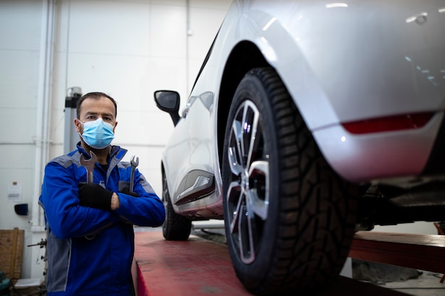 Porträt des professionellen automechanikers, der gesichtsmaske wegen des koronavirus trägt, der in fahrzeugwerkstatt durch fahrzeug steht.