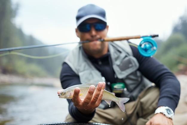 Porträt des professionellen fischers, der regenbogenforelle im gebirgsfluss zeigt. glücklicher mann, der seinen fang während des lieblingshobby an der frischen luft hält.