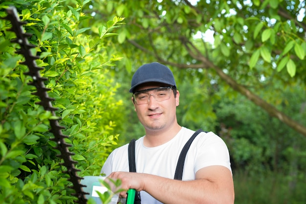 Porträt des professionellen gärtners, der trimmer hält, der im hof arbeitet