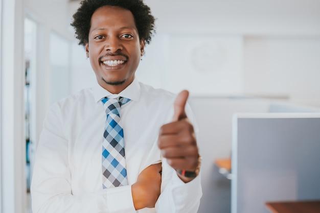 Porträt des professionellen geschäftsmannes, der daumen oben zeigt, während er im modernen büro steht.