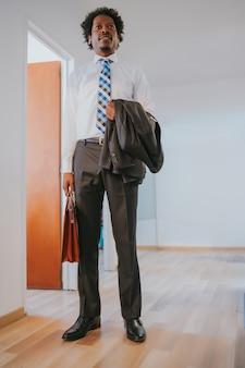 Porträt des professionellen geschäftsmannes, der eine aktentasche hält, während am modernen büro steht. unternehmenskonzept.