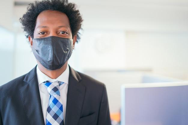 Porträt des professionellen geschäftsmannes, der gesichtsmaske trägt, während am modernen büro steht. neuer normaler lebensstil. unternehmenskonzept.
