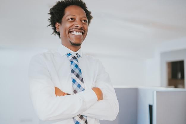 Porträt des professionellen geschäftsmannes lächelnd, während am modernen büro stehend. geschäfts- und erfolgskonzept.