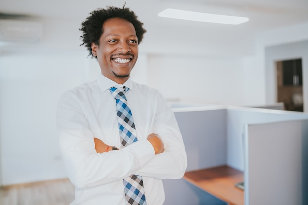 Porträt des professionellen geschäftsmannes lächelnd, während am modernen büro stehend.