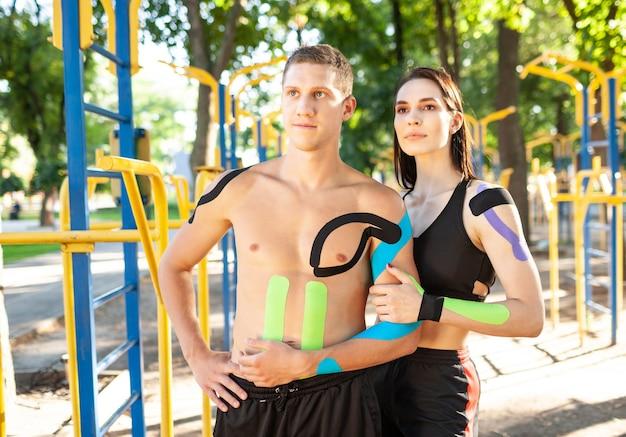 Porträt des professionellen kaukasischen athletenpaares, des gutaussehenden mannes und der brünetten frau mit kinesiologischem taping auf körpern, posierend am sportplatz, beiseite schauend.