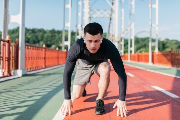 Porträt des professionellen läufers am start bereit zum sprint. sportmann, der musik mit drahtlosen kopfhörern im freien hört