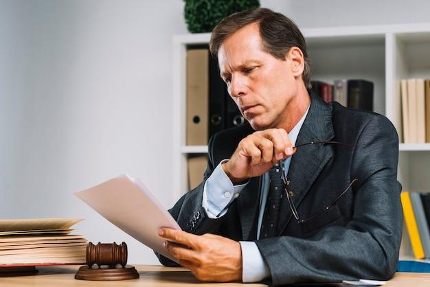 Porträt des professionellen reifen rechtsanwaltlesedokuments im gerichtssaal