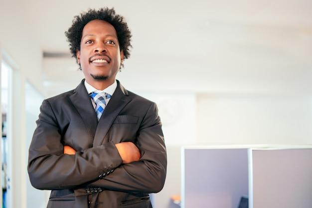 Porträt des professionellen und selbstbewussten geschäftsmannes, der lächelt, während er am modernen büro steht. geschäfts- und erfolgskonzept.