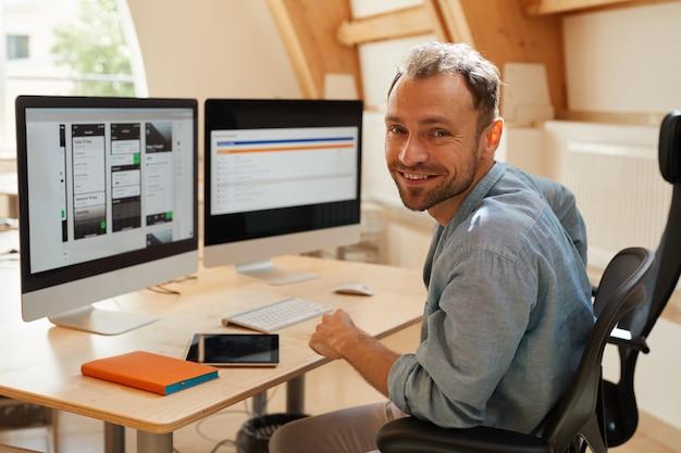 Porträt des programmierers, der in die kamera lächelt, während er an seinem arbeitsplatz mit computermonitoren sitzt und mit software arbeitet